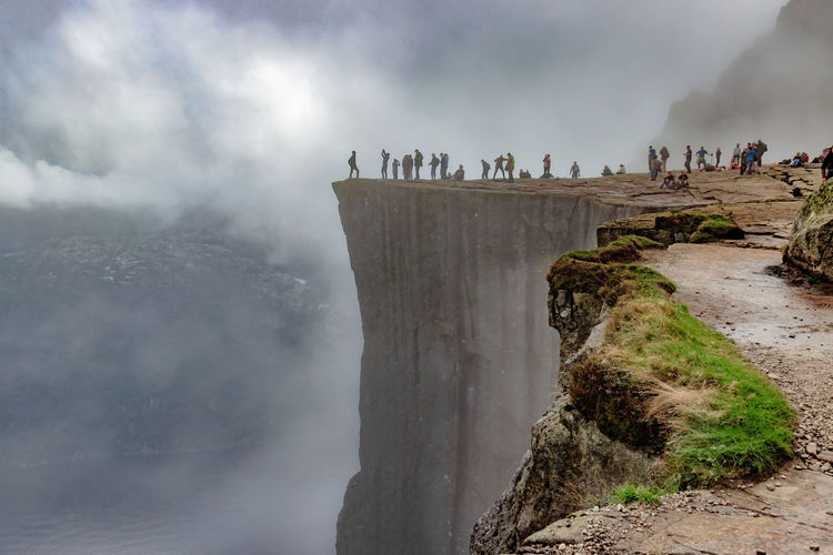 People On Cliff Against Cloudy Sky During Foggy Weather