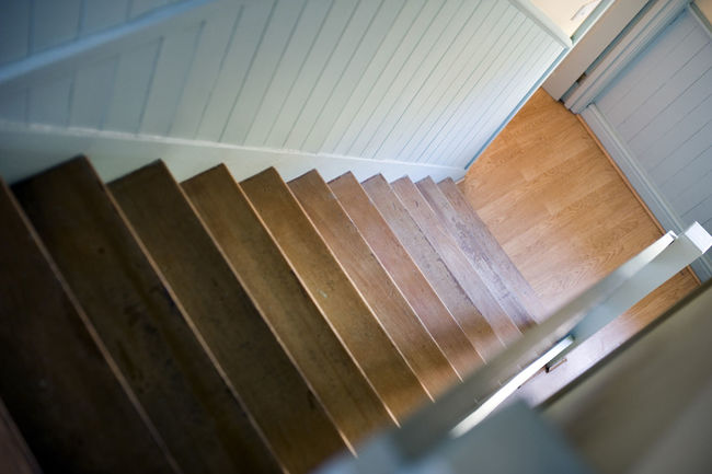 View from the top looking down a flight of interior stairs with wooden treads to a passage below Architecture Descending Down Downwards Interior Overhead Passageway Staircase Stairs Steps Treads View Walls Wooden