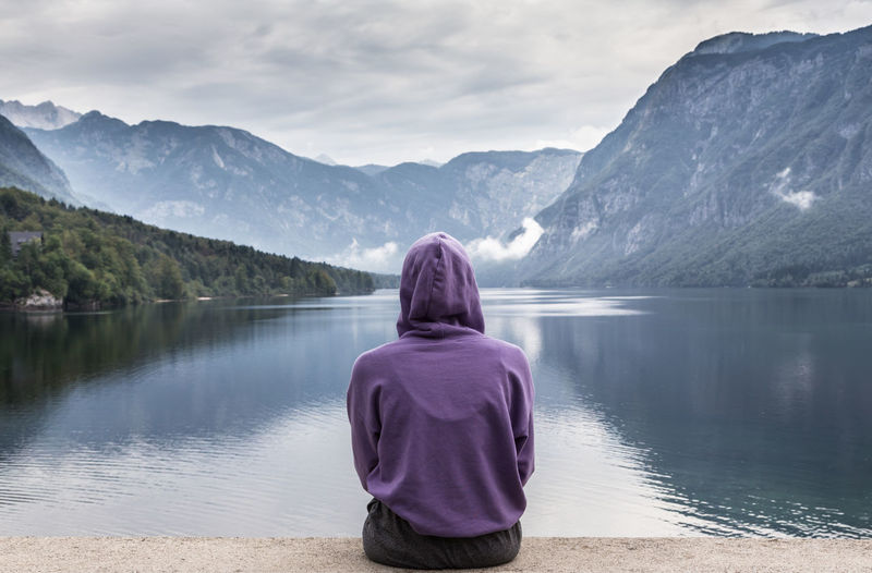 Rear view of woman wearing hoodie looking at lake against mountain