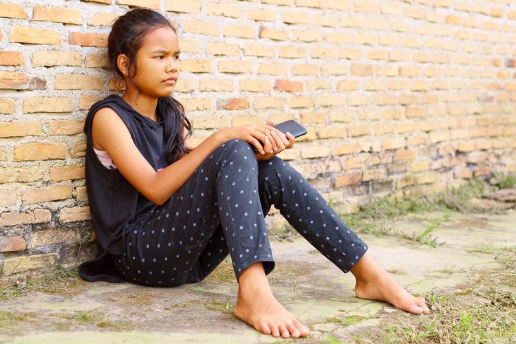 Full length of teenage girl sitting against brick wall