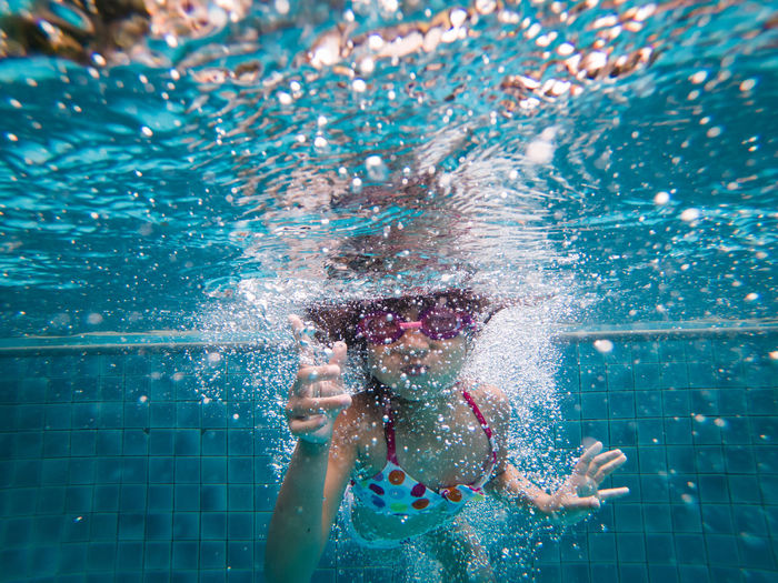 Cheerful Asian little girl diving and swimming in pool on summer vacation. Fun Goggles Holiday Child Chinese Enjoyment Eyewear Fun Kid Leisure Activity Lifestyles Little Girl Nature Outdoors People Pool Positive Emotion Real People Splashing Summer Swimming Swimming Pool Swimwear Underwater Water