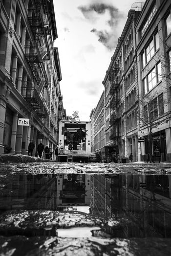 Reflection. Street Mood. New York Streetphotography Streetphoto_bw Street Photography Building Exterior Architecture Built Structure Building City Water Reflection Cloud - Sky Sky Waterfront Nature No People Residential District Day Street Puddle Outdoors Canal Transportation Surface Level EyeEmNewHere