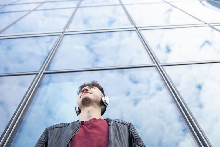 Low angle portrait of young man against sky