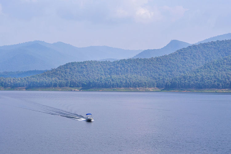 Scenic view of lake and mountains against sky.