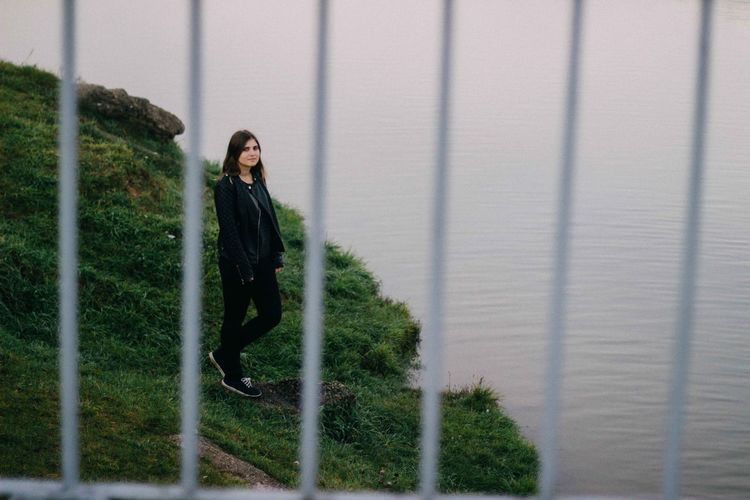 Full length of young woman standing by lake seen through railing