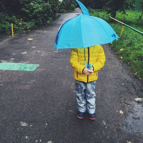 Child With Blue Umbrella Standing On Street