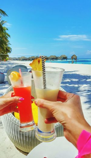 Close-up of women toasting fresh drinks at beach