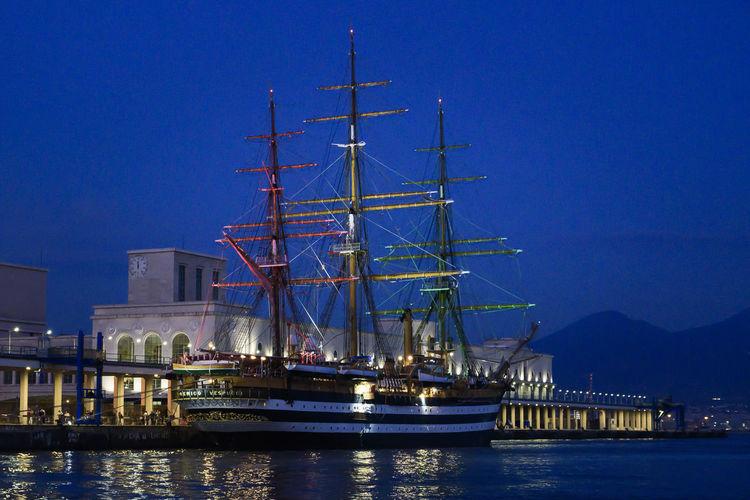 Sailboats sailing in sea against sky at night
