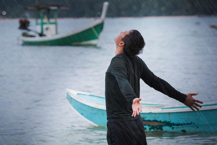 Man enjoying rain at seashore