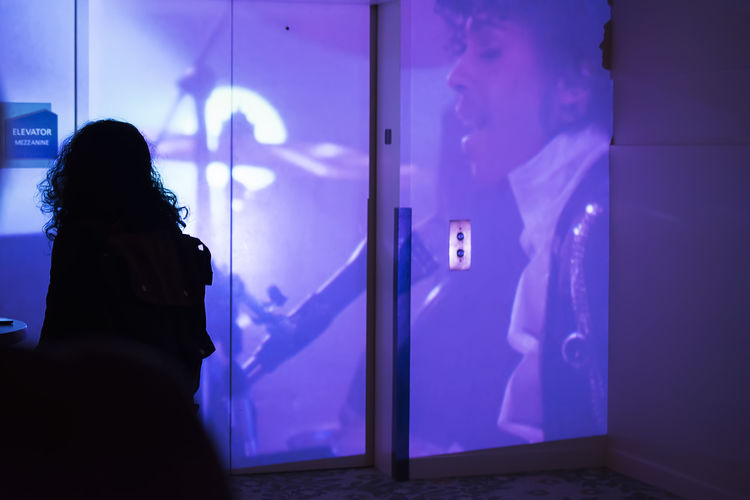 "A woman looks on as a scene from ""Purple Rain"" is projected in memorial to world famous musician Prince, as part of Ritual: (Sub) Urban Projections at the Hult Center in Eugene, Oregon on April 21st 2016. Art Blue Illuminated Performance Performance Art Prince  Projection Purple Silhouette"