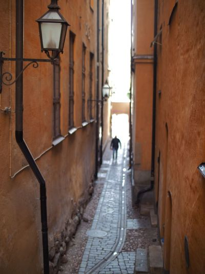Rear view of man walking on narrow street