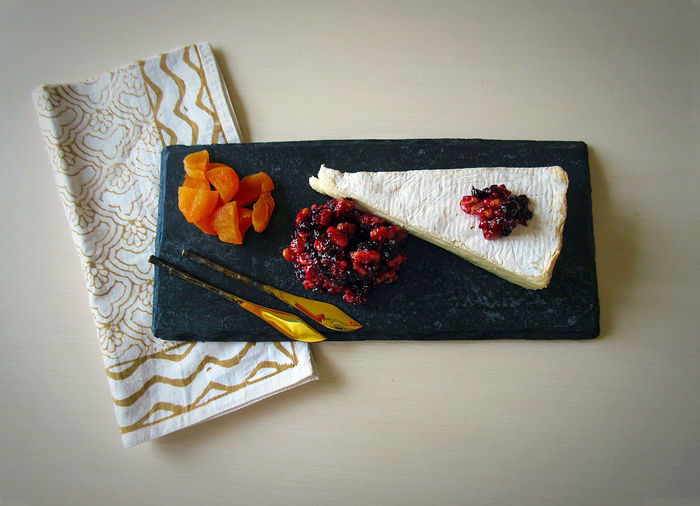 Directly above shot of brie with cranberry chutney on granite