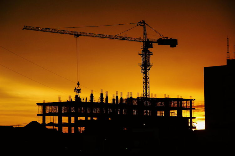 Silhouette crane at construction site during sunset