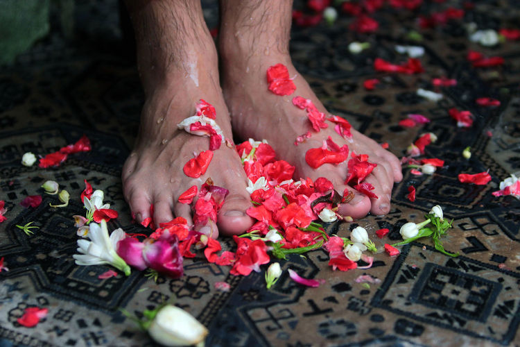 Low section of man with red petals on floor