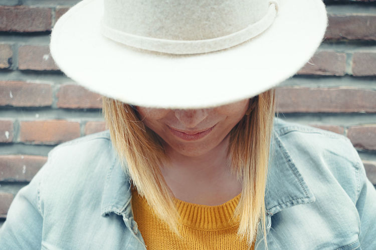 Close-up of smiling woman wearing hat against brick wall