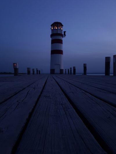 Lighthouse amidst buildings against sky at dusk