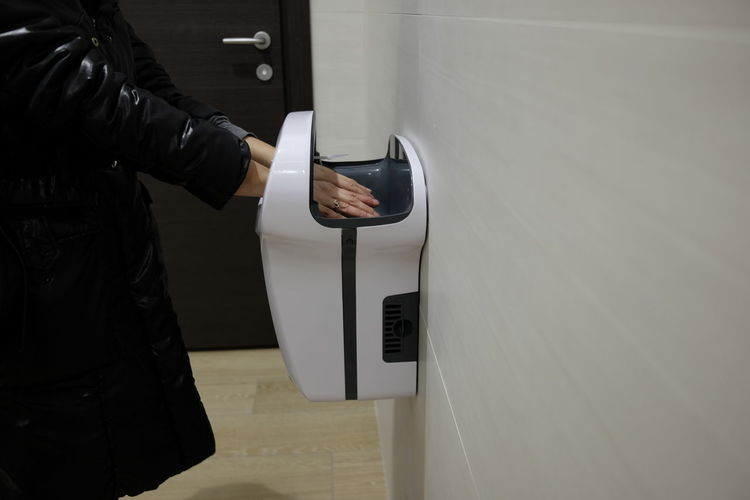 Midsection of woman using hand dryer