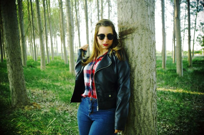 Portrait of woman wearing sunglasses while standing by tree at forest