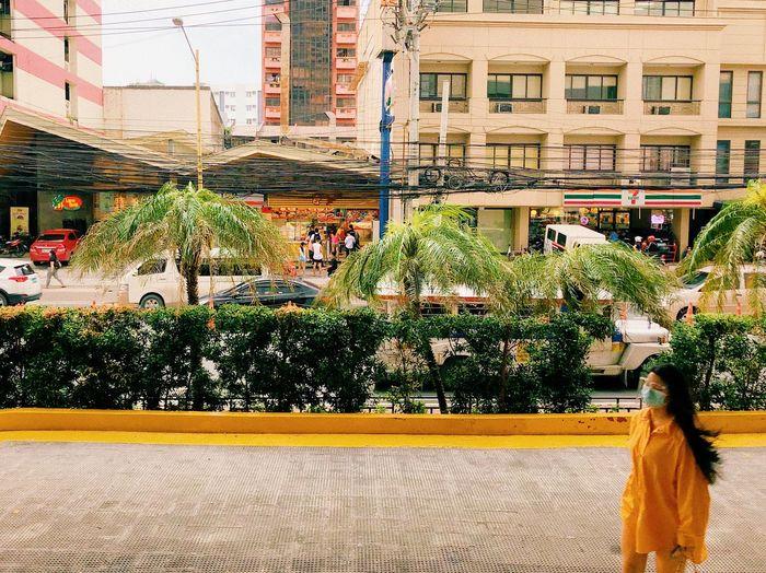 Rear view of woman walking on street against buildings in city