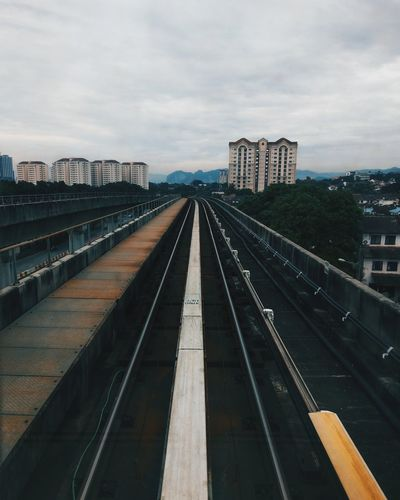 Railroad Tracks In City Against Cloudy Sky