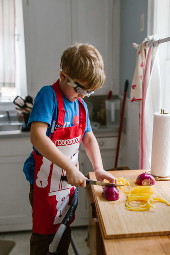 Boy Cutting Onion In Kitchen At Home