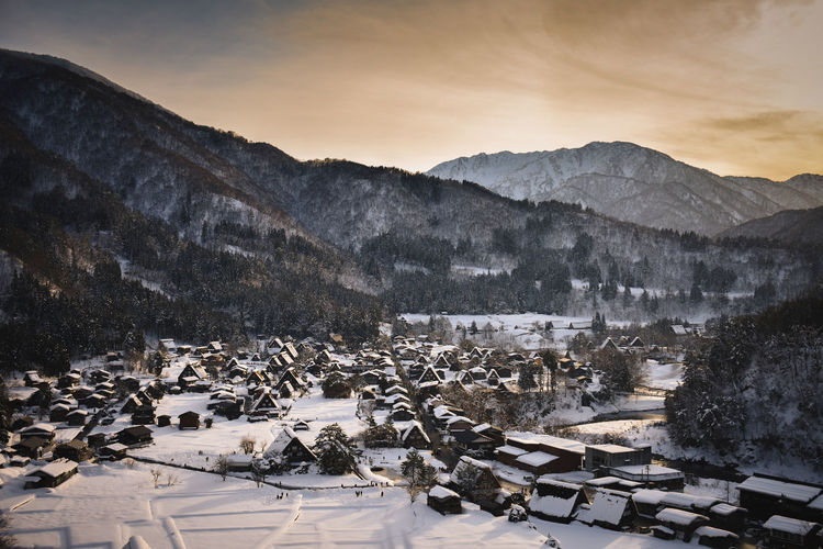 High angle view of snowcapped mountain against sunset in shirakawa-go village japan hut