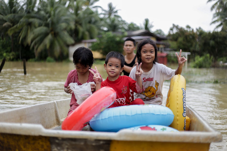 flood victims at kelantan Flood Victim Boys Childhood Day Elementary Age Enjoyment Family Father Girls Happiness Leisure Activity Lifestyles Mid Adult Mid Adult Men Mother Outdoors Real People Sitting Smiling Son Togetherness Tree Water Young Adult Young Women