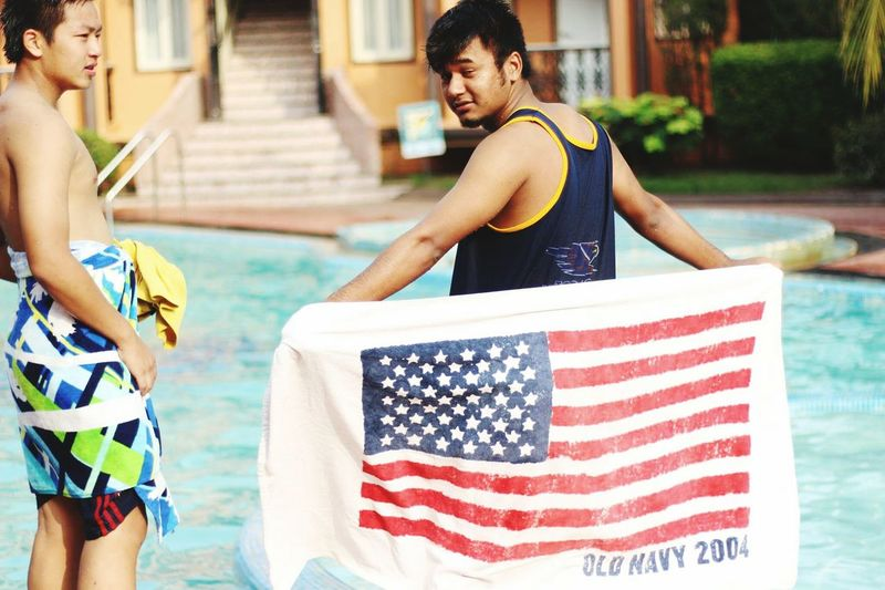 Rear view of man holding american flag while standing by swimming pool