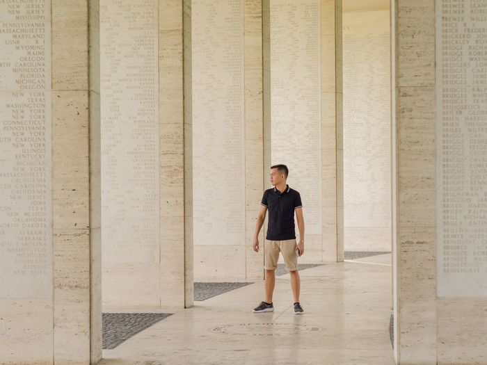Full length of young man standing by columns at colonnade