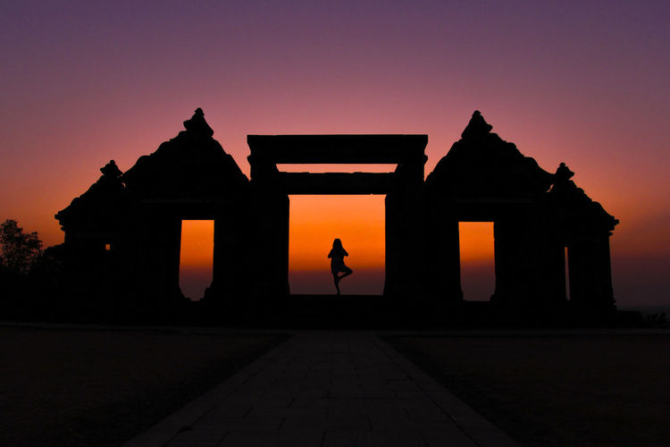 Silhouette person doing yoga at gateway of ratu boko ruins against clear sky