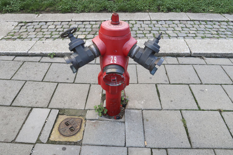 Antwerp, Belgium - December 4, 2018; Red old fashioned fire pump and Iron gas manhole cover on a walking street in Antwerp Fire Hydrant Footpath Day Safety High Angle View Protection Outdoors Street City Antwerp, Belgium Fire Pump Manhole Cover Sidewalk Red Paving Stone