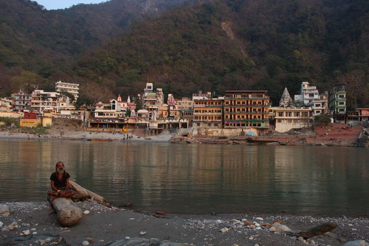 Sadhu sitting on driftwood by ganges river against city