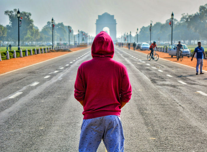 Rear View Of A Man Standing On Road