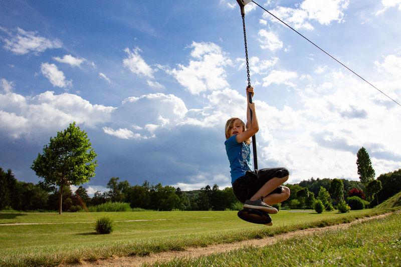 Full Length Of Boy Zip Lining Against Sky On Field