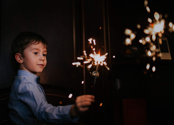 Boy looking while holding sparkler at night