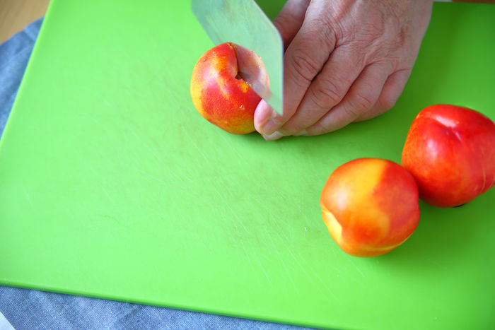 Cutting a nectarine with copy space Copy Space Man Natural Light Cutting Cutting Board Day Dish Cloth Fingers Food Food Preparation Fresh Fruit Green Color Hand Healthy Eating Holding Indoors  Kitchen Knife Nectarines One Person Overhead Red Studio Shot