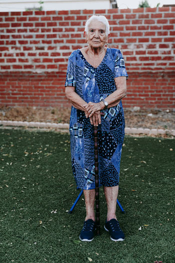 Portrait of smiling senior woman standing against brick wall