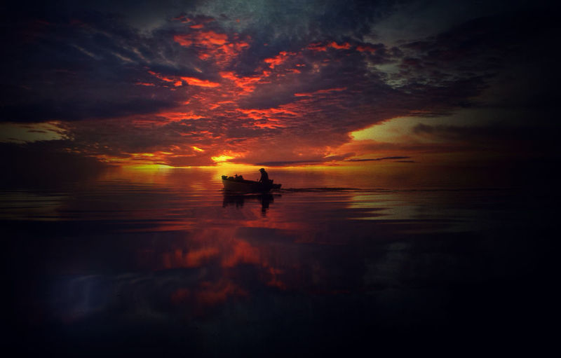 Silhouette Boat In Sea Against Dramatic Sky During Sunset