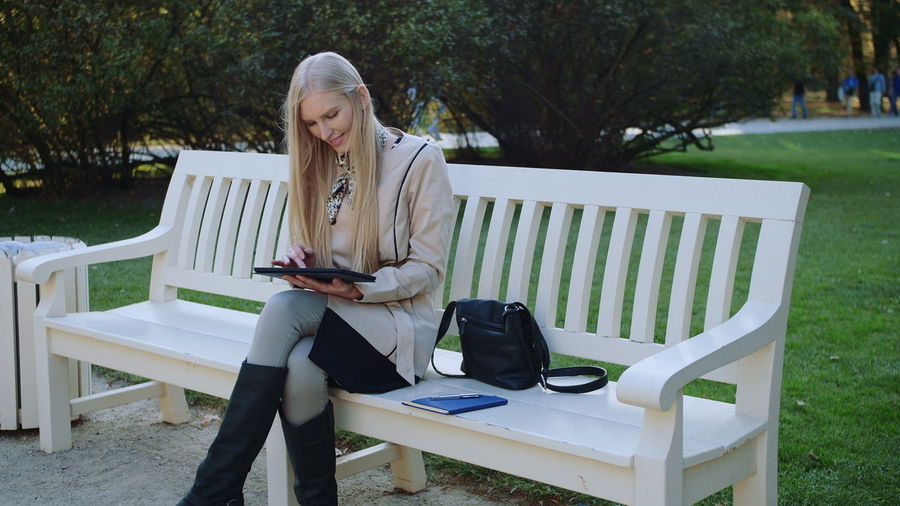 Woman using digital tablet while sitting on bench in park