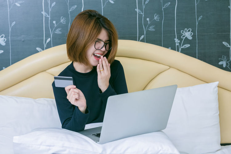 Smiling young woman doing online shopping over laptop while sitting on bed against wall at home