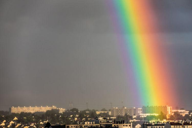 Rainbow over illuminated buildings in city against sky
