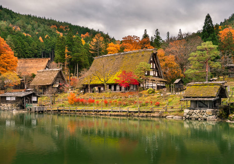 Houses by lake and buildings against sky during autumn