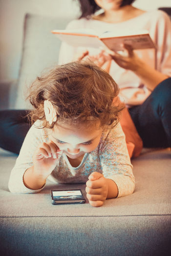 Cute small girl surfing the net on smart phone while relaxing at home with her mother.