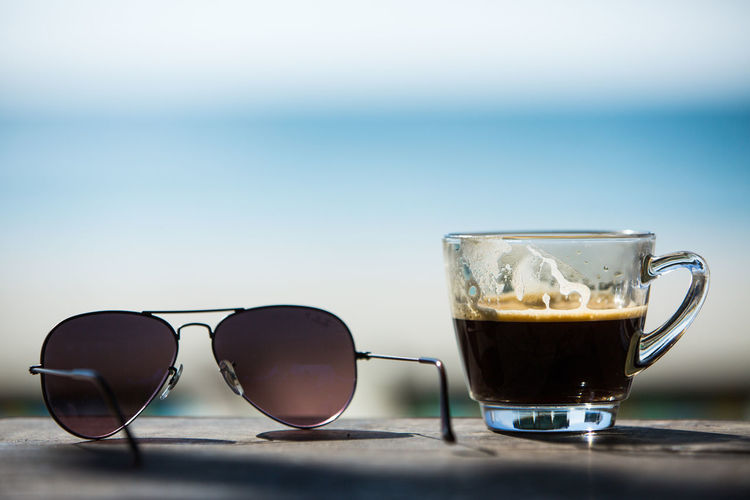 Coffee cup and Sunglasses on wood table with beach chairs & sand Background Coffee Coffee Time Refreshment Relaxing Beach Close-up Coffee - Drink Coffee Cup Copy Space Cup Drink Drinking Glass Focus On Foreground Food And Drink Glass Glasses Mug Refreshment Sand Sea Sea And Sky Seascape Still Life Table Thailandtravel