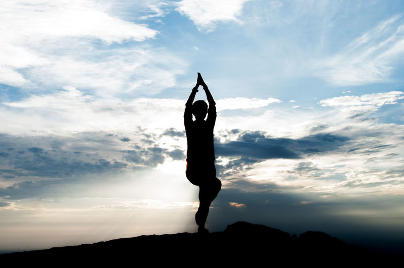 Silhouette Person Doing Yoga Against Cloudy Sky At Dusk