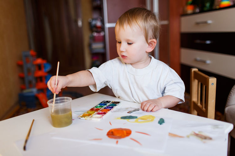 Boy painting with watercolors