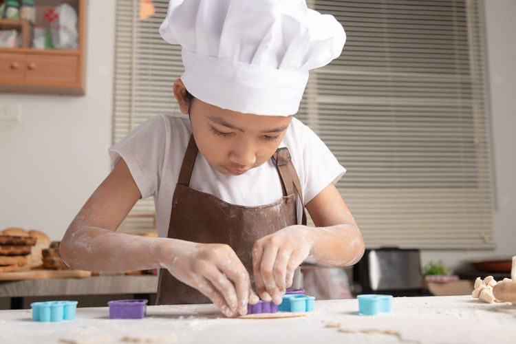 The little asian girl wore a white chef hat and a brown apron. the kid making cookies