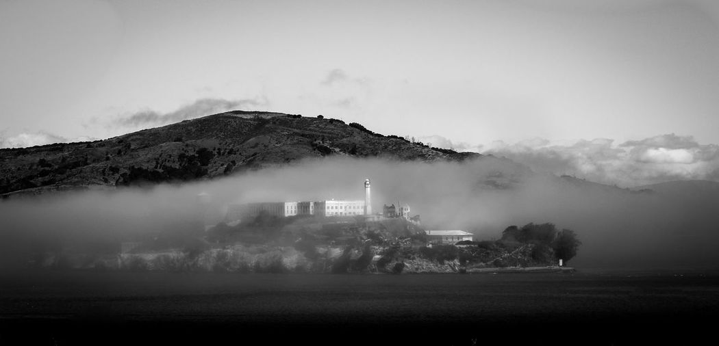 Alcatraz island in sea against mountain in foggy weather