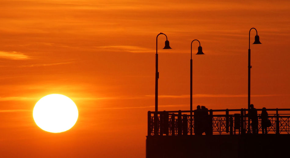 Silhouette street light by sea against orange sky in tuscany