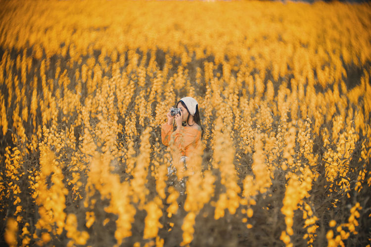 Young woman photographing while standing amidst flowering field